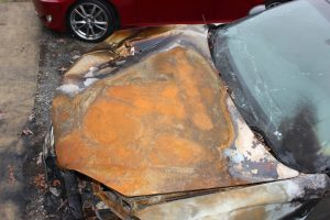 Photo showing fire patterns on the hood of a burned car.